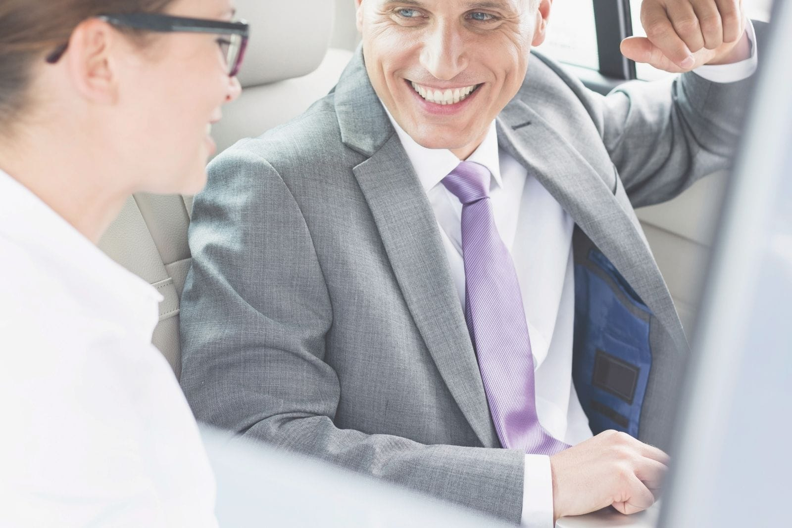 smiling male and female colleagues talking in the car