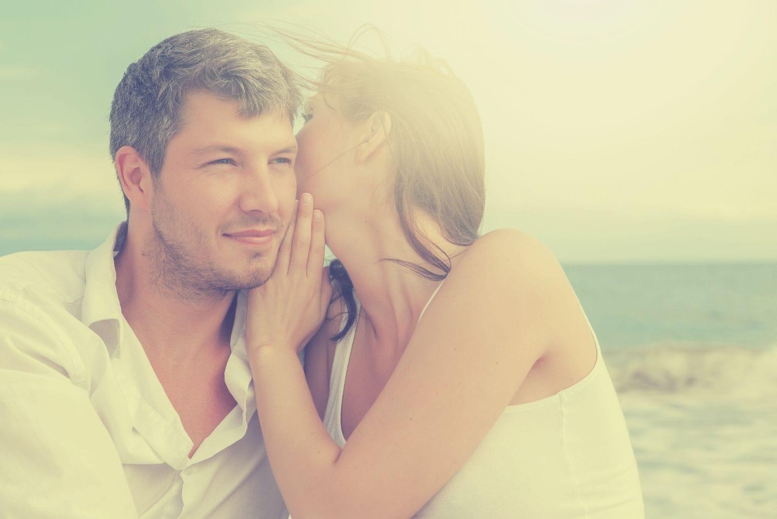 sun shiny behind the couple whispering sweetly sittingoutdoors