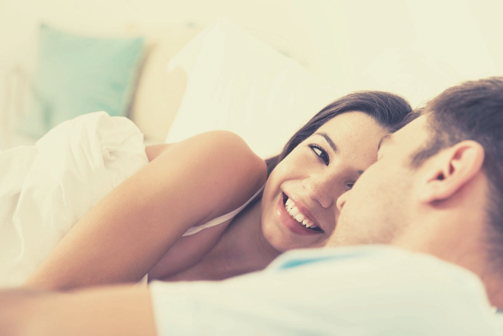 sweet couple in bed looking at each other smiling while lying down