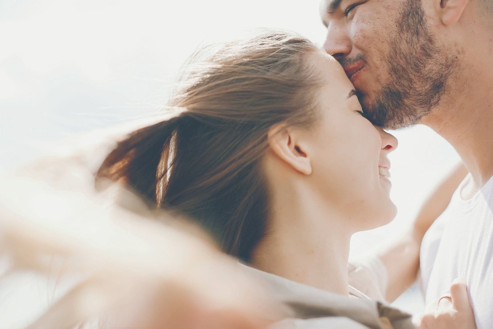 tender and merry lovers enjoying with boyfriend kissing the woman's forehead in close up image