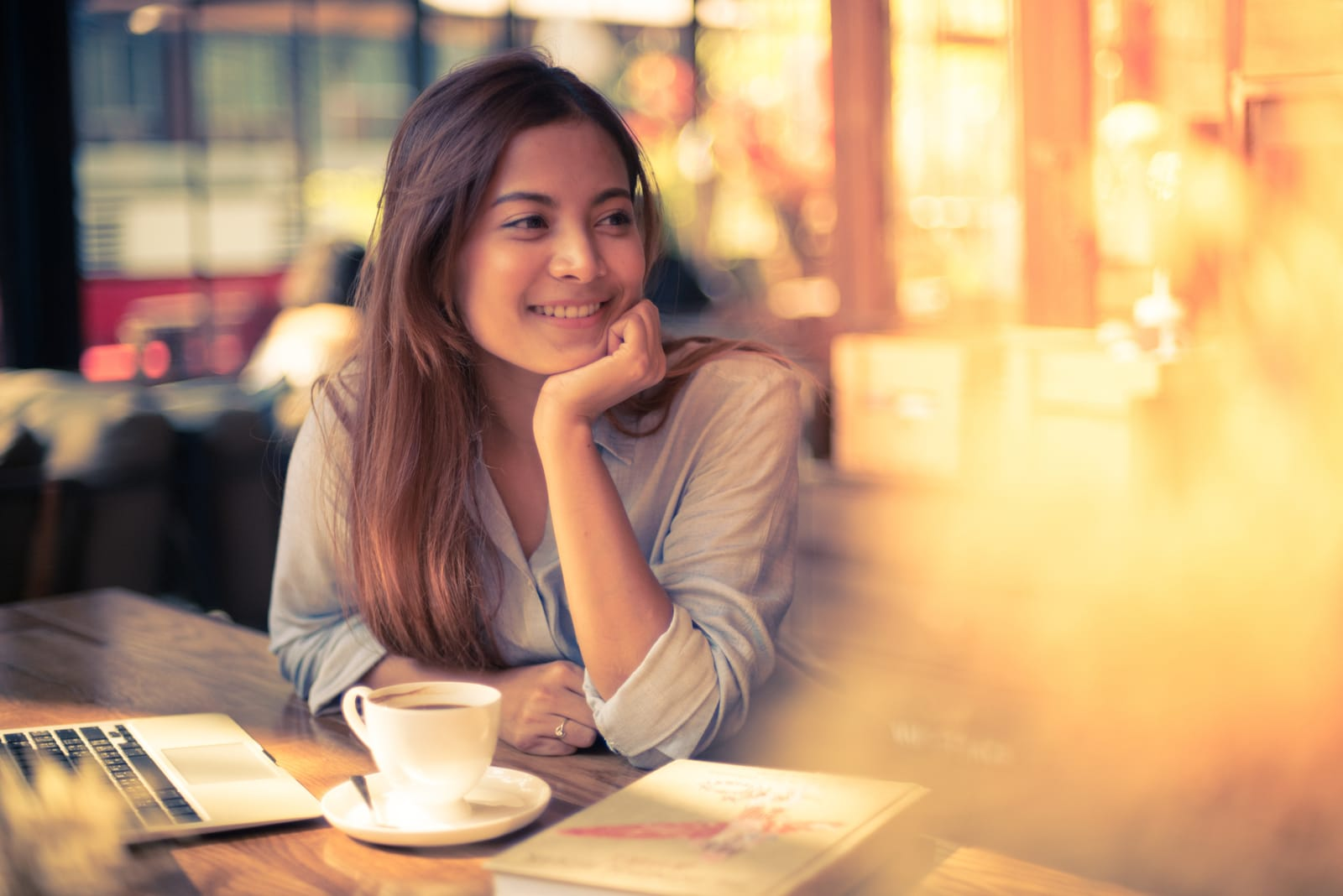 the woman sits drinking coffee and looks away