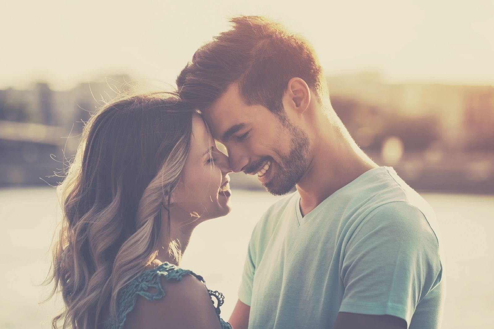 toned image of a couple with both forehead touching and smiling while hugging standing in the beach