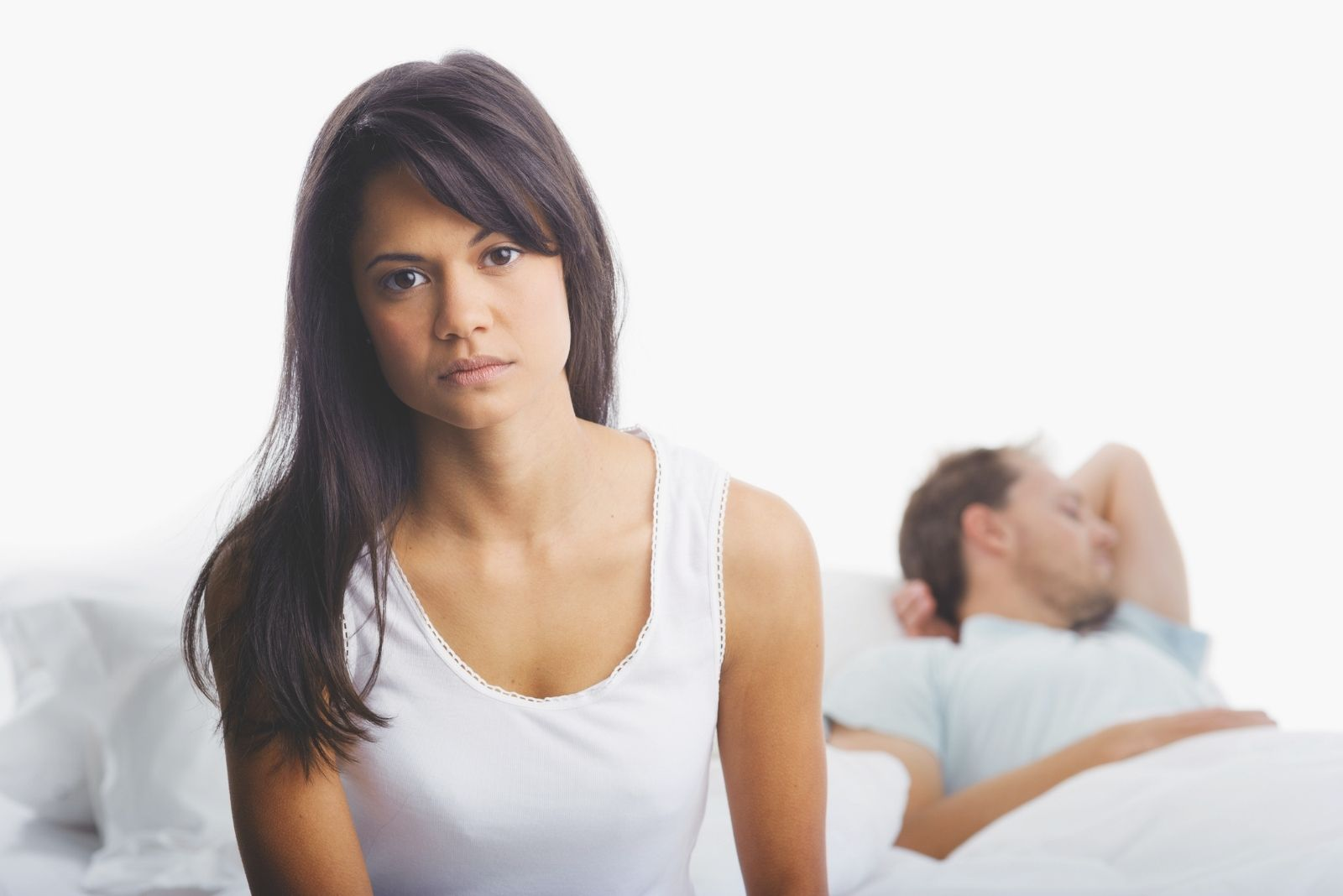 upset woman sitting in bed with a man sleeping in the background