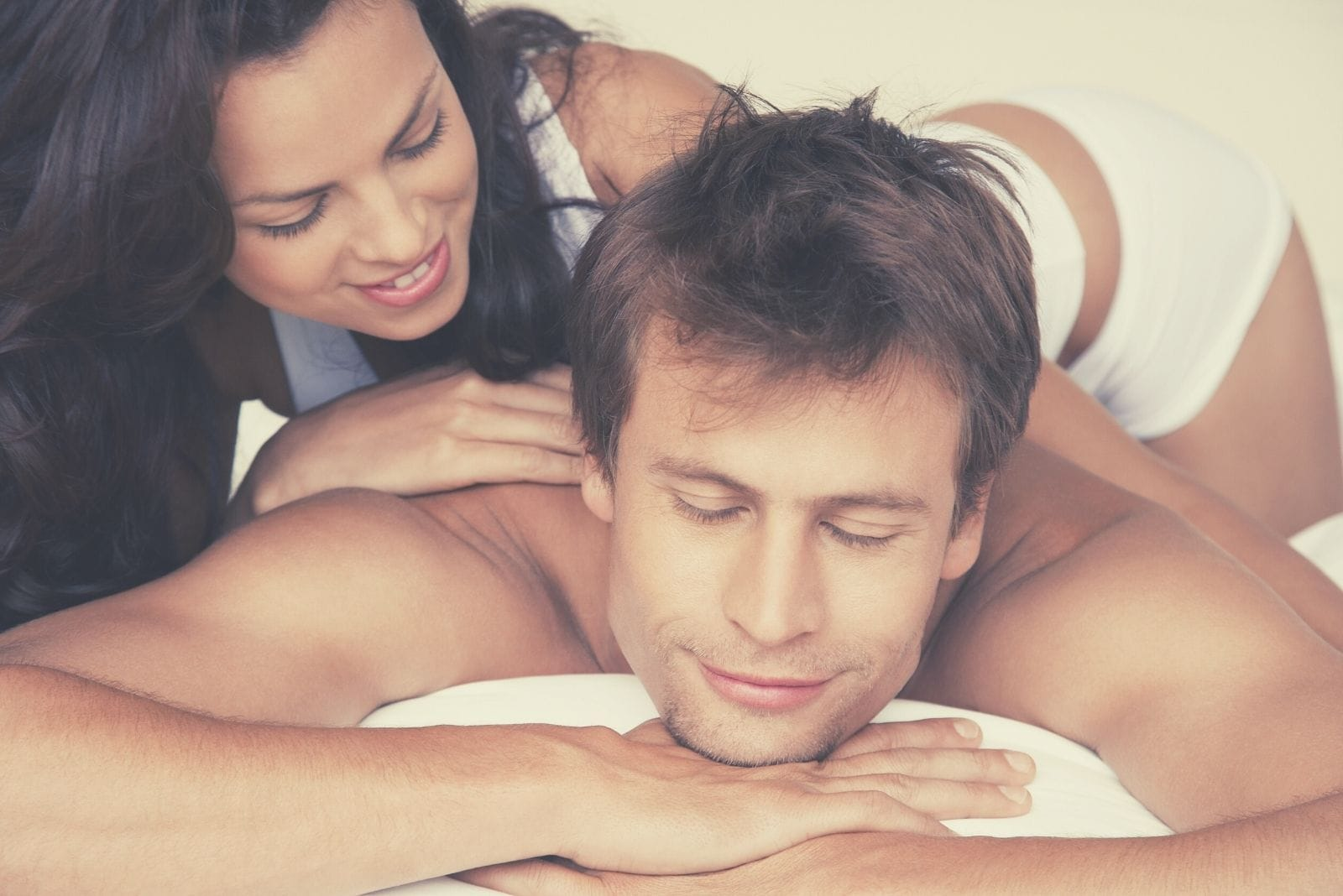 wife giving massage to her husband closing his eyes lying down