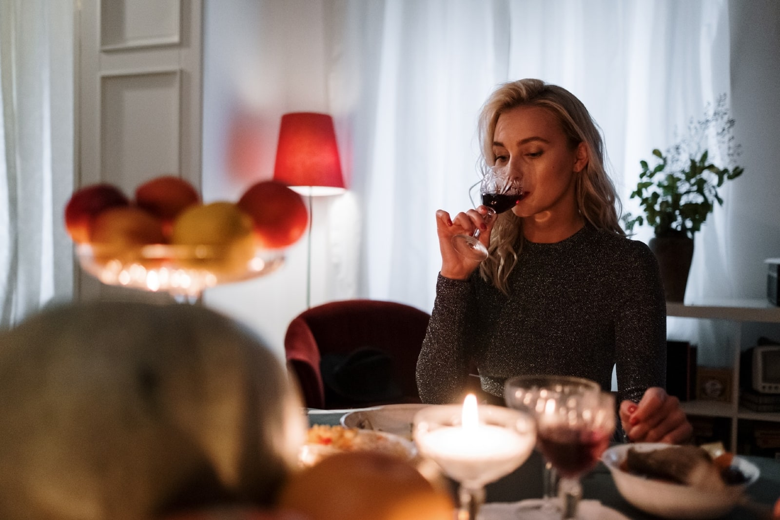 woman drinking wine while sitting at table