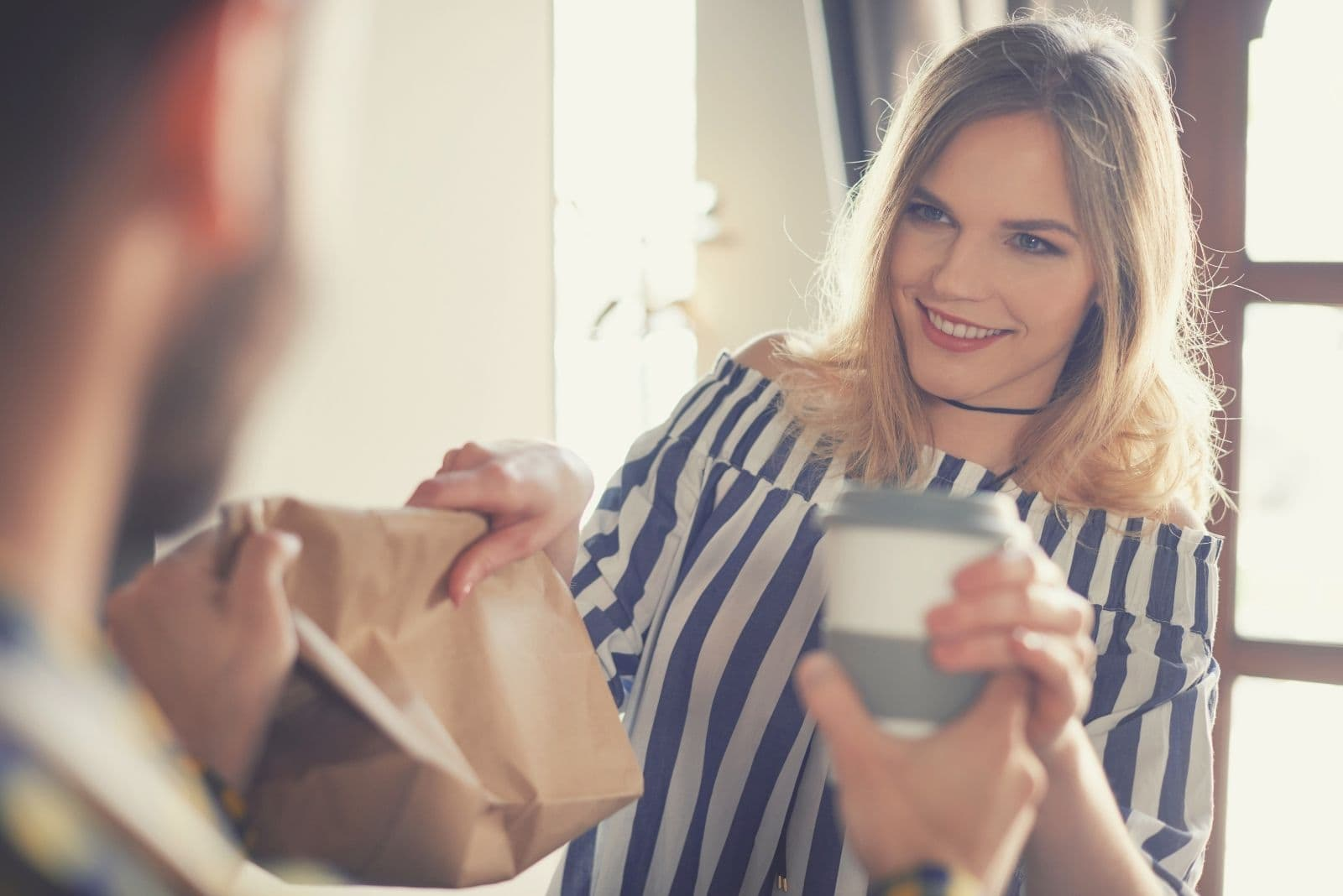 woman handling over pack and coffee to a man
