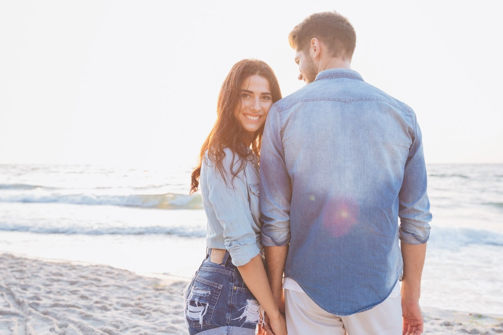 woman holding her boyfriend in hand while looking at the camera and smiling standing in the shore