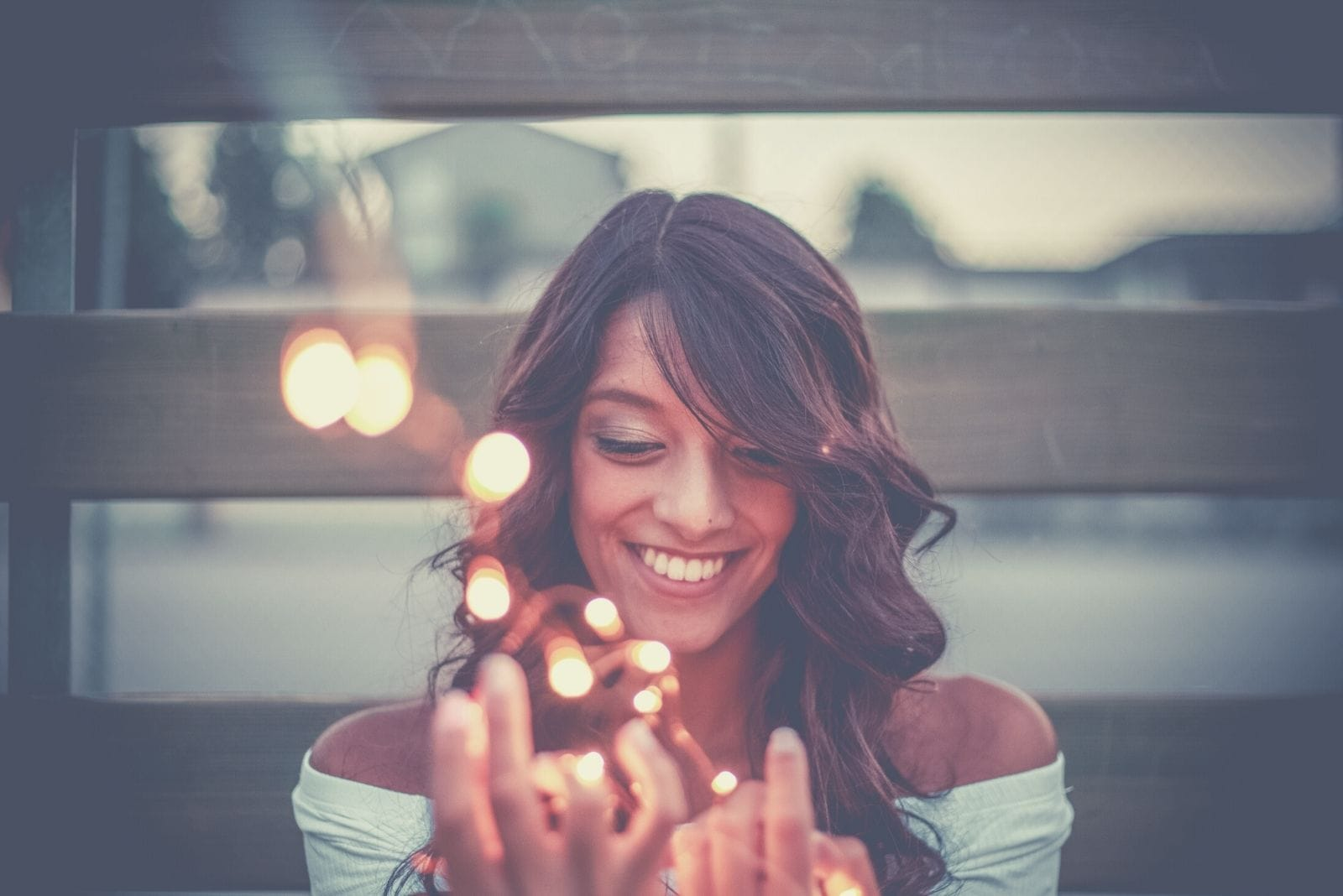 woman holding lights smiling and sitting outdoors
