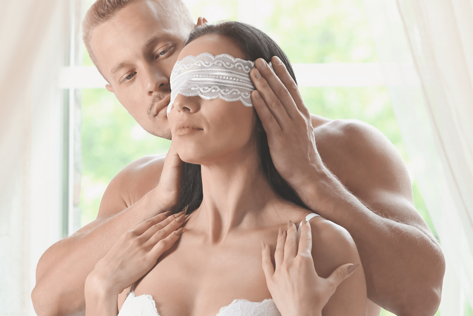 woman in lingerie blindfolded by a shirtless man