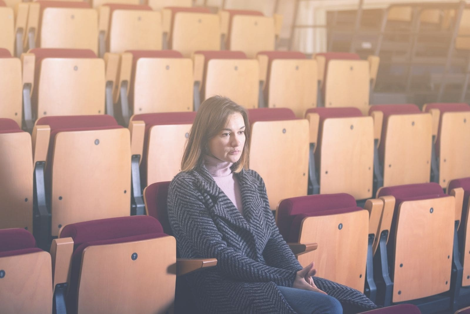 woman in the movie house alone waiting and pensive with empty seats