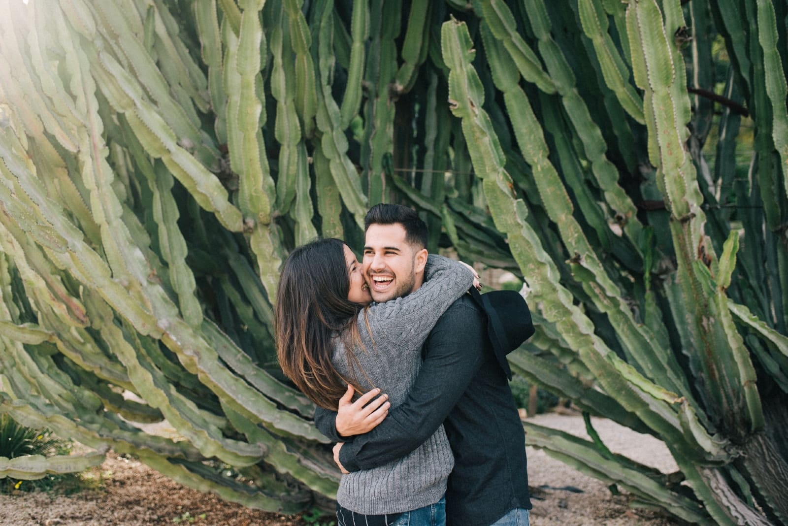 woman kissing man while standing near cactus