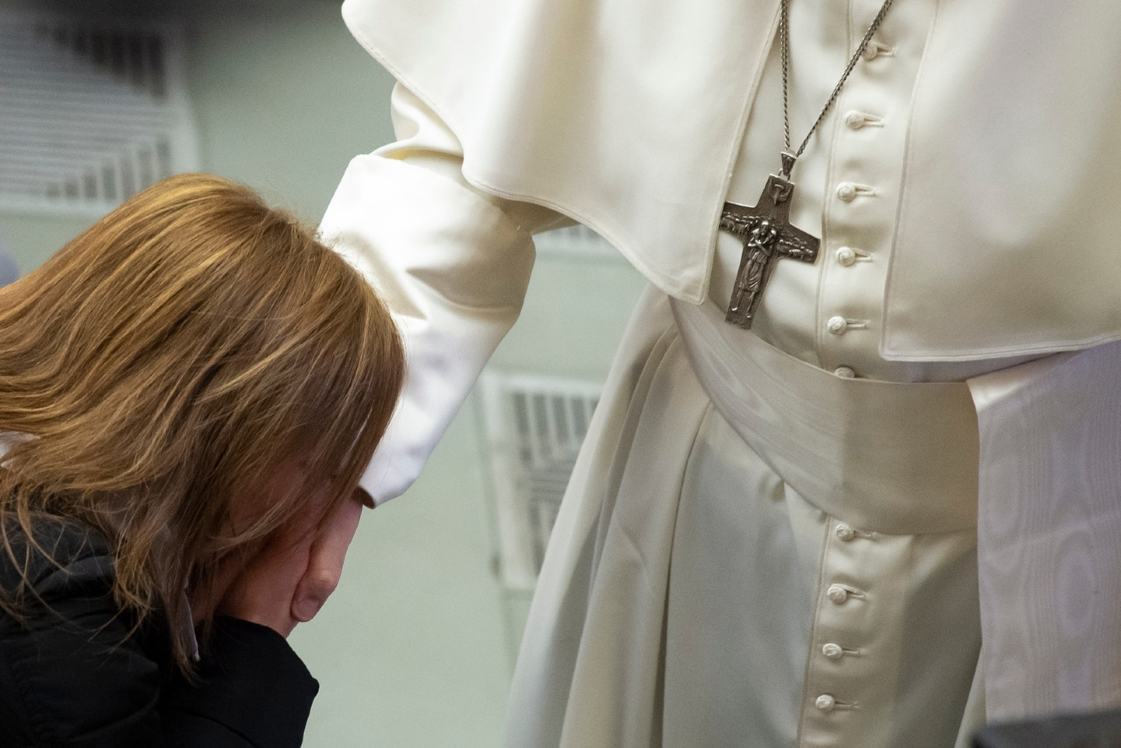 woman in black jacket kissing pope's hand in vatican