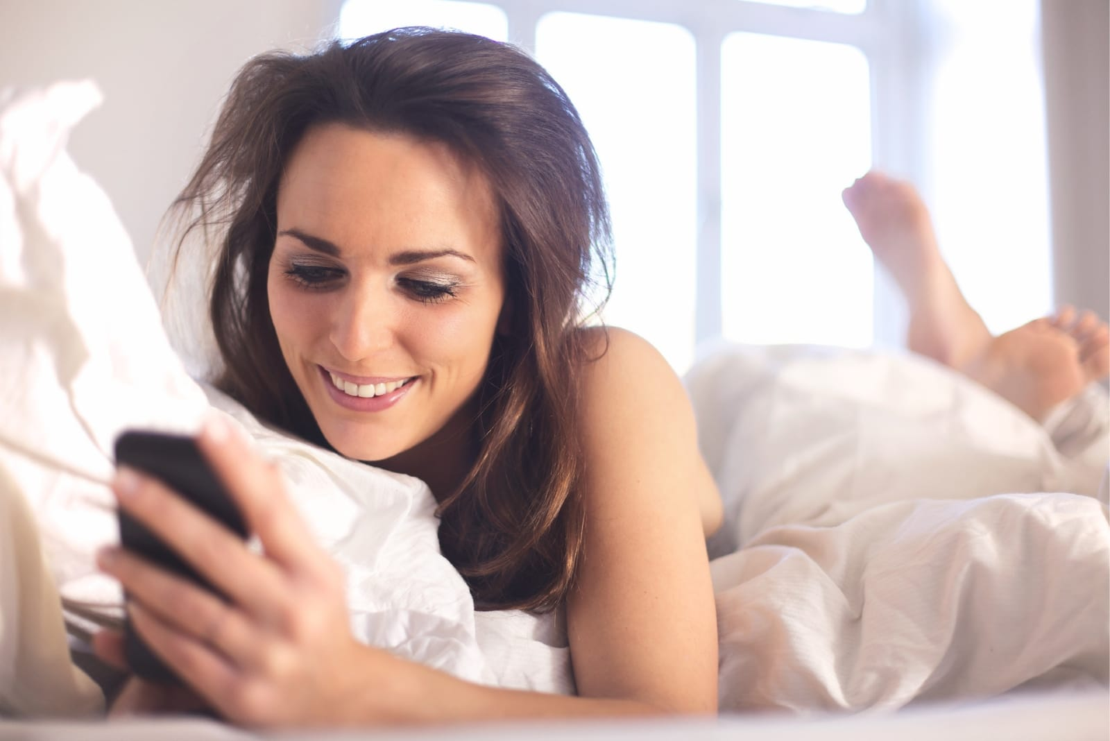 woman looking at phone while laying on bed