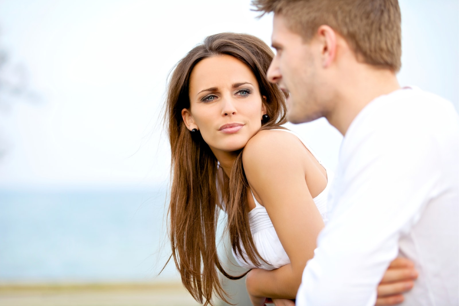 serious woman in white top listening to man