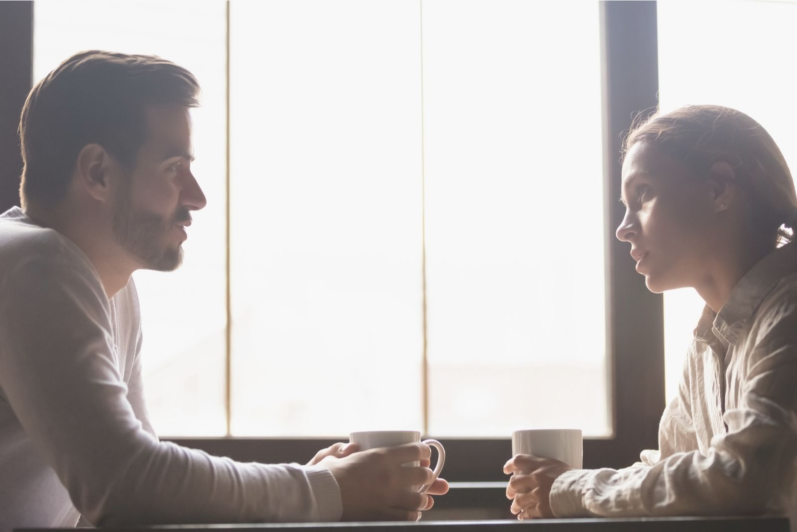 woman listening to the man talking about problems inside a cafe