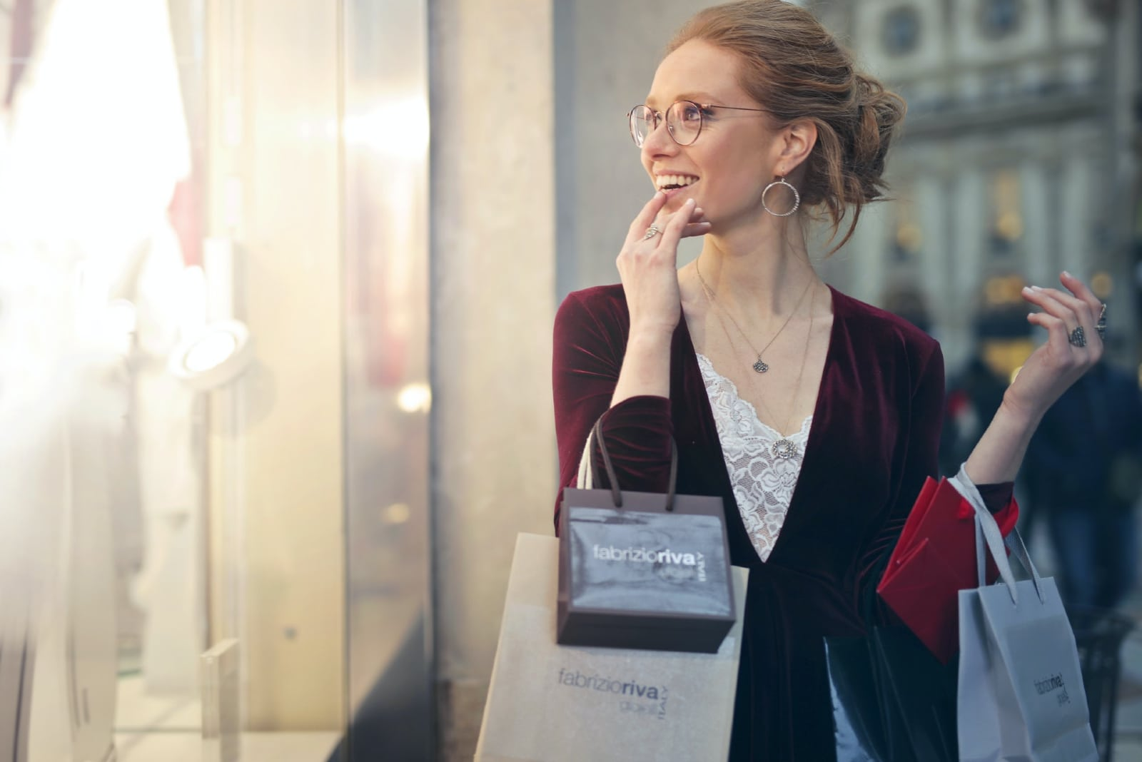 woman looking at storefront while holding shopping bags