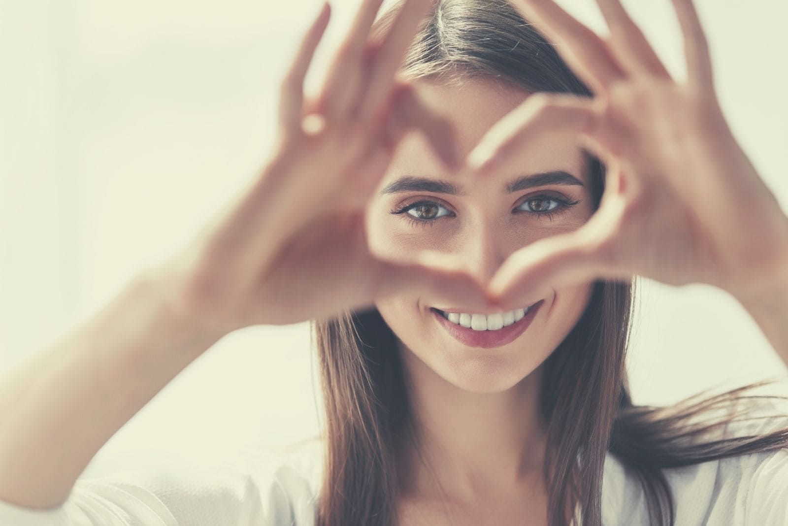 woman making hand sign of heart shaped focus on the face
