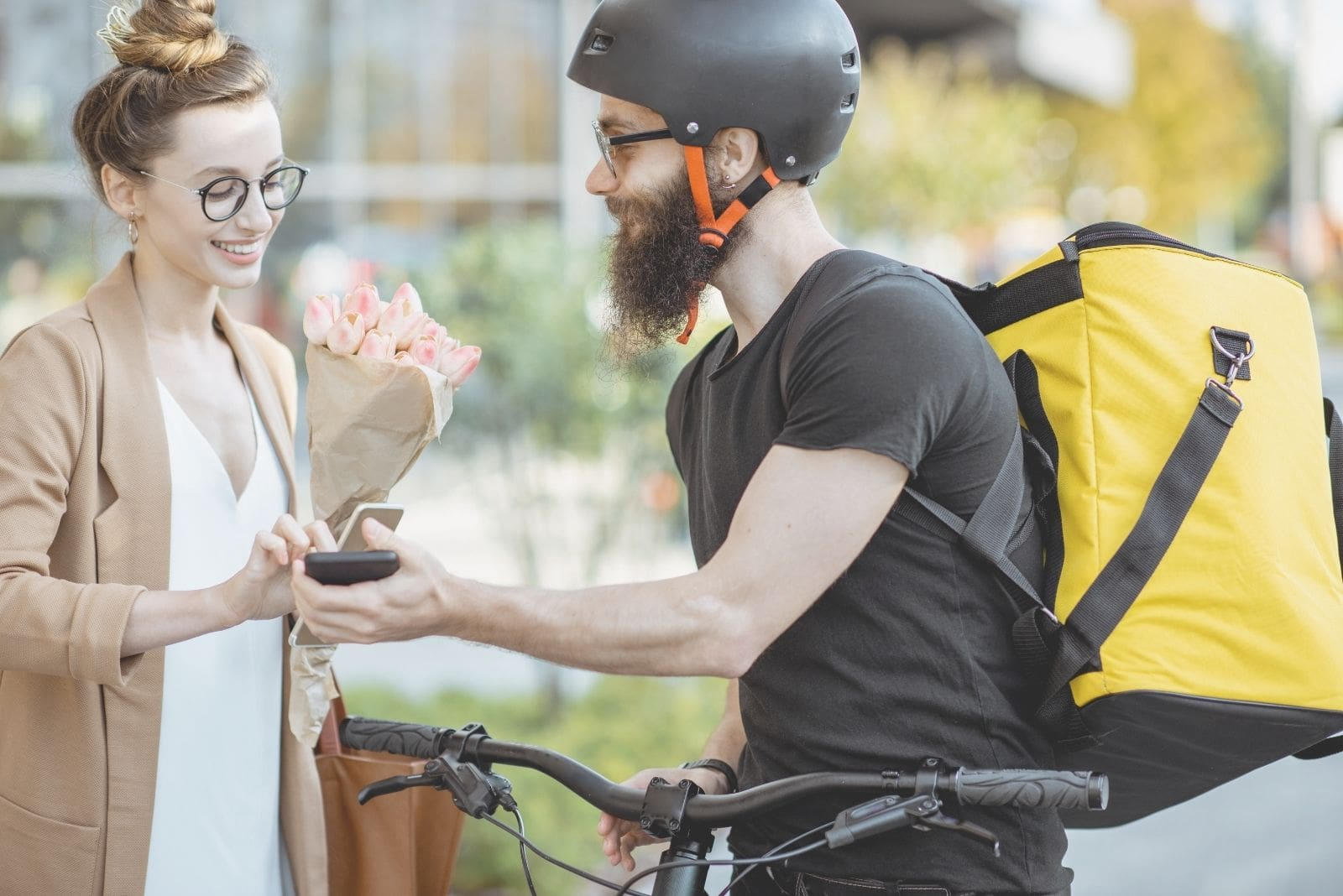 woman receiving flowers from the delivery guy in a bike holding a receipt gadget