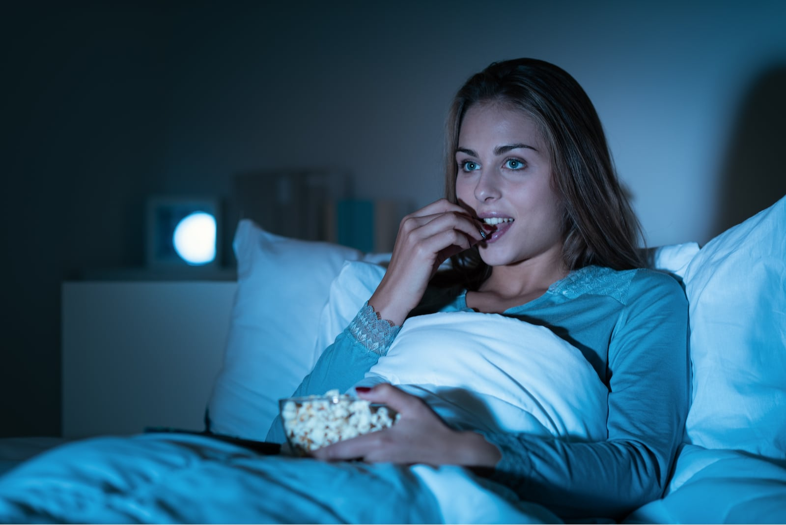 happy woman relaxing in bed and watching movies