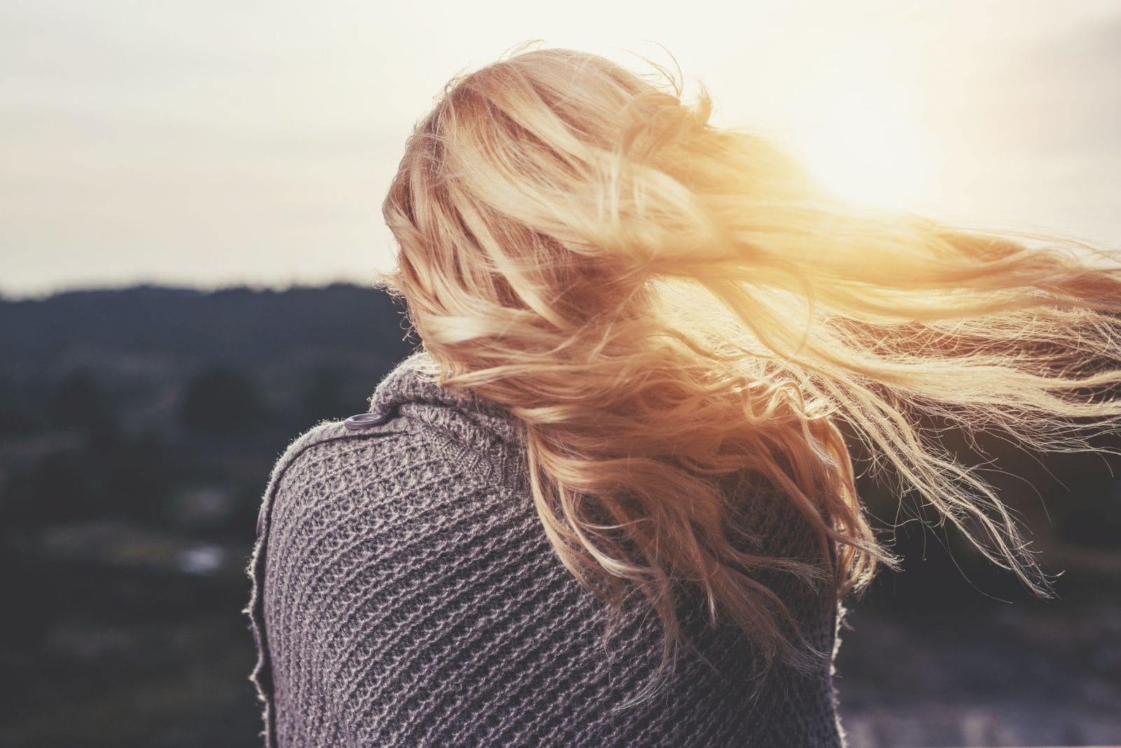 woman showing her back while facing the sunrise with blonde hair blown by the wind