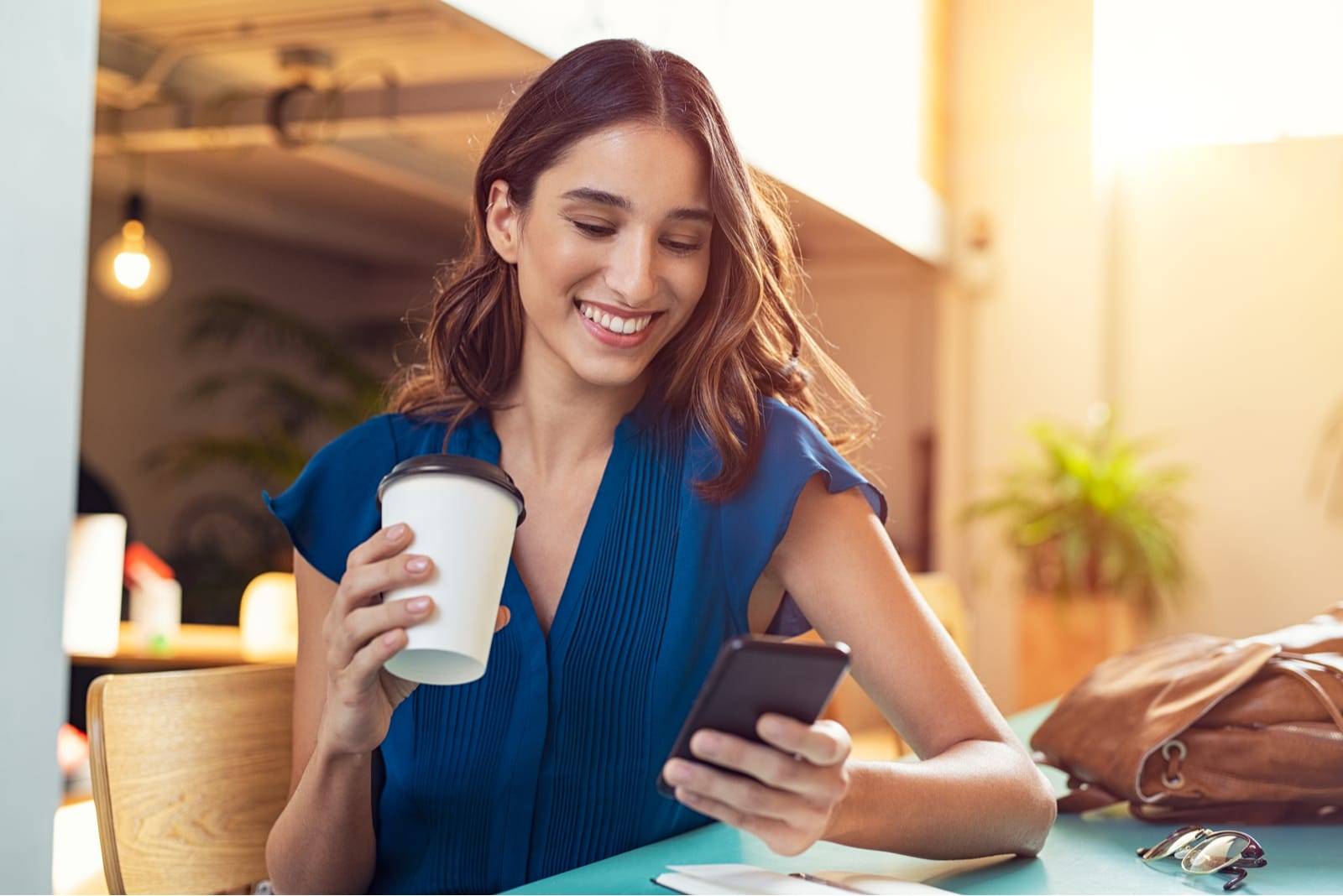 woman sitting drinking coffee and key on the phone