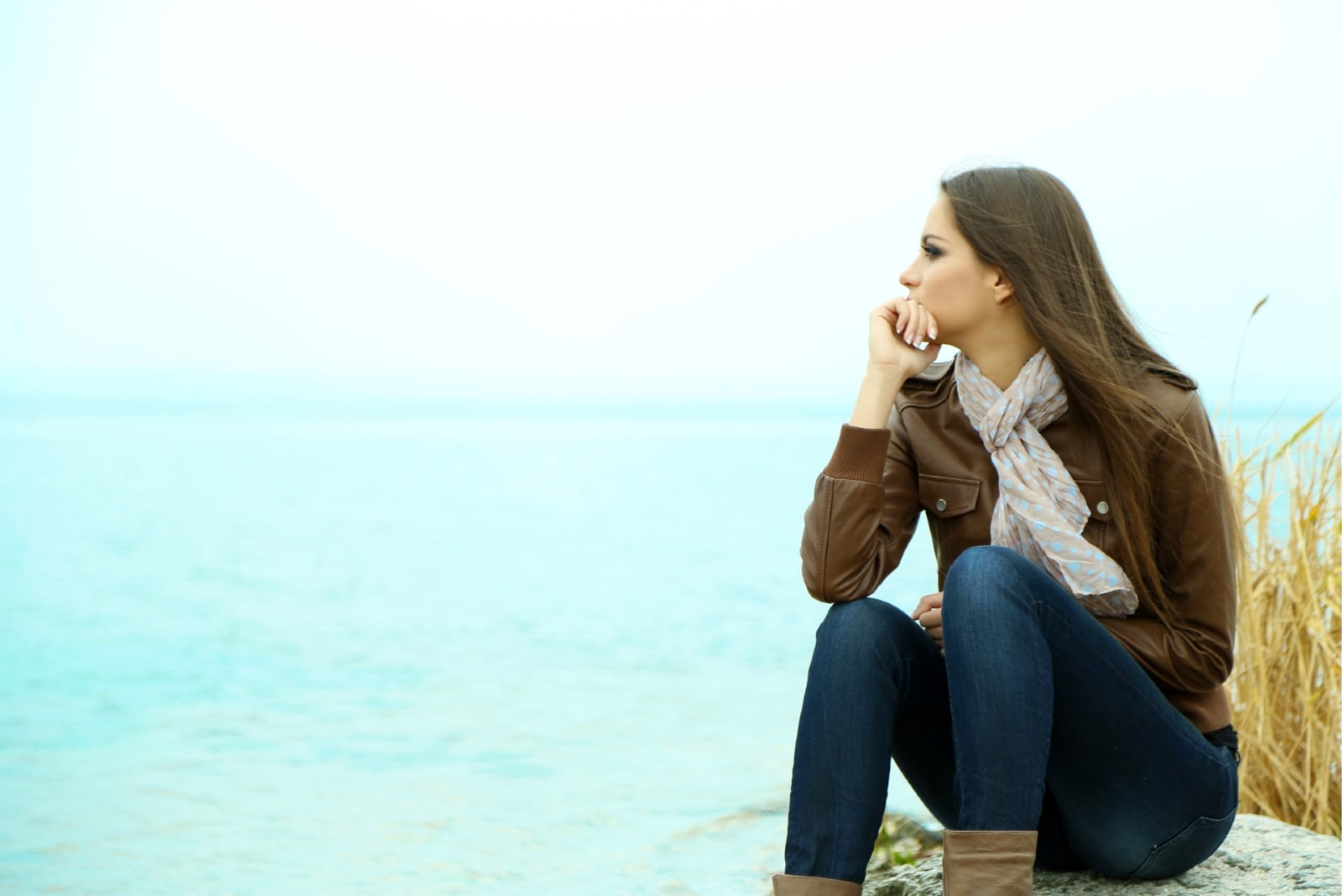 pensive woman in brown jacket sitting near water