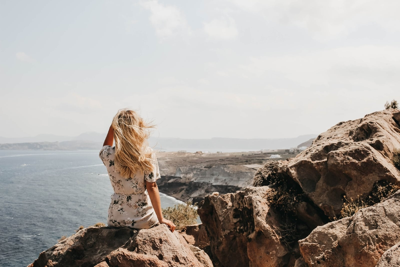 blonde woman sitting on rock looking at sea
