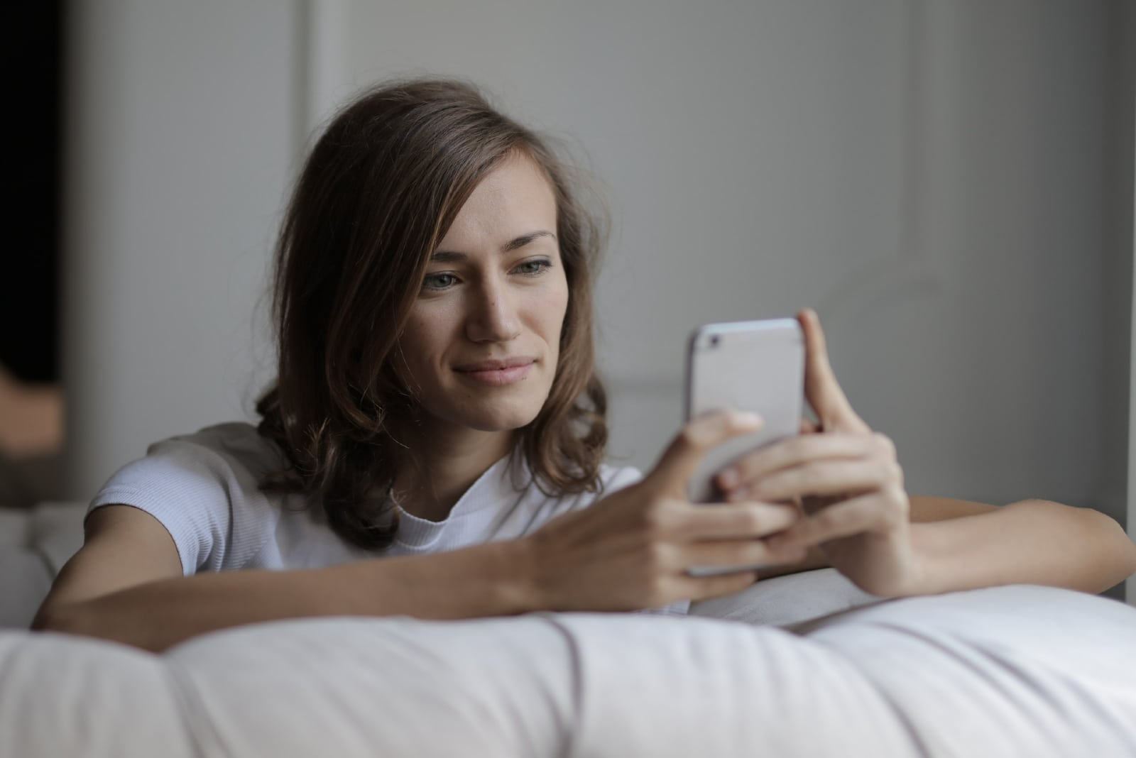 woman using smartphone while sitting on sofa