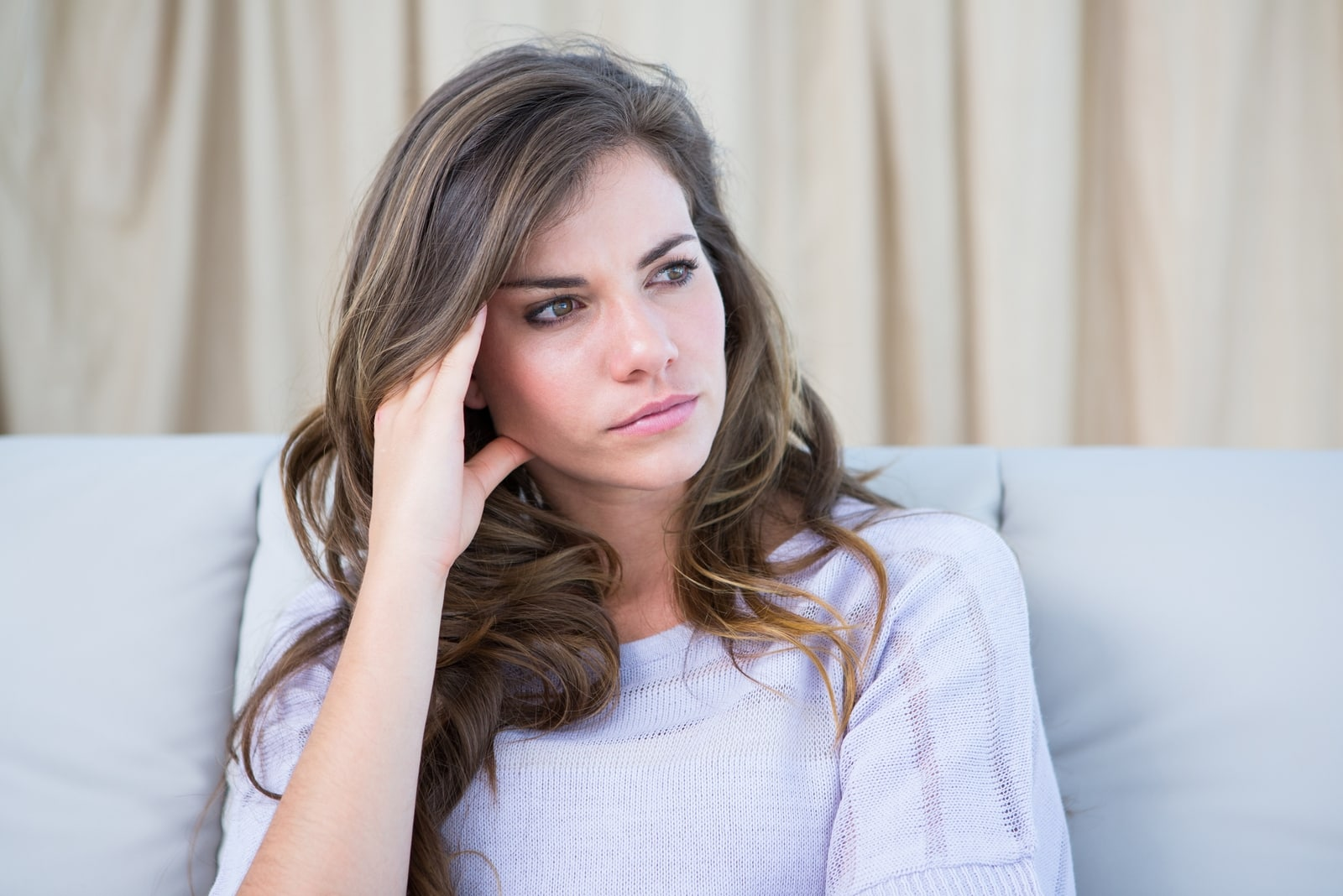 pensive woman in white top sitting on sofa