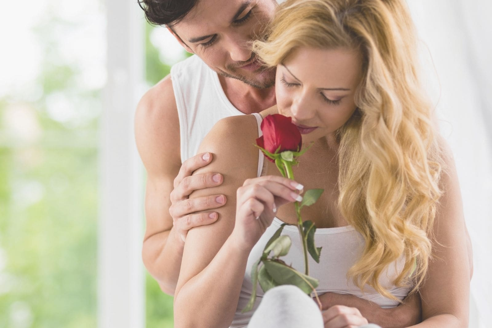 woman smelling a rose given by his romantic husband hugging her