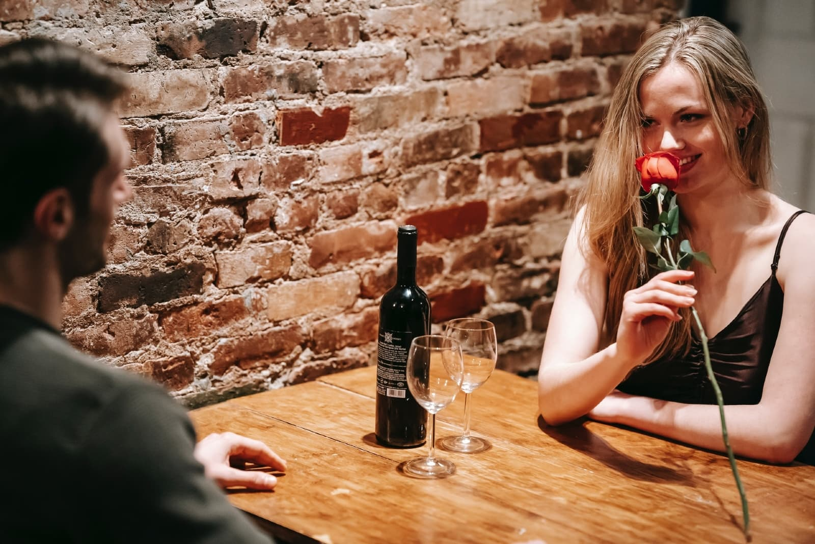 woman smelling red rose while sitting at table