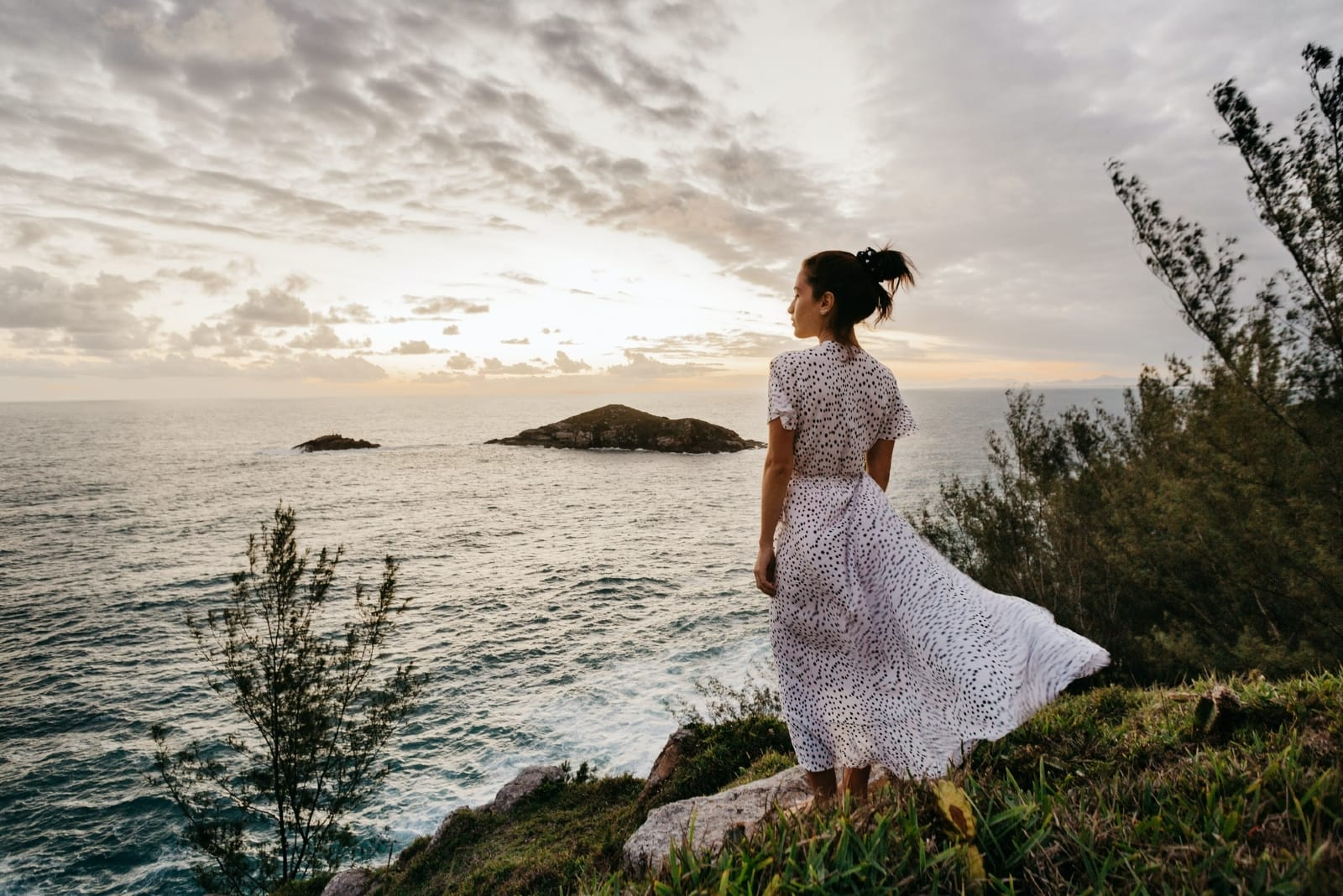 woman in white printed dress standing near sea