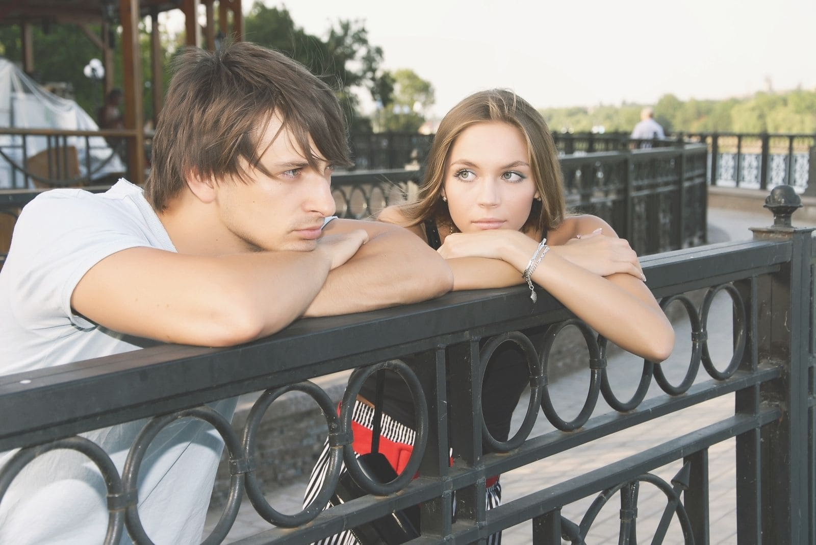 woman staring at the man leaning on the railings outdoors standing beside her