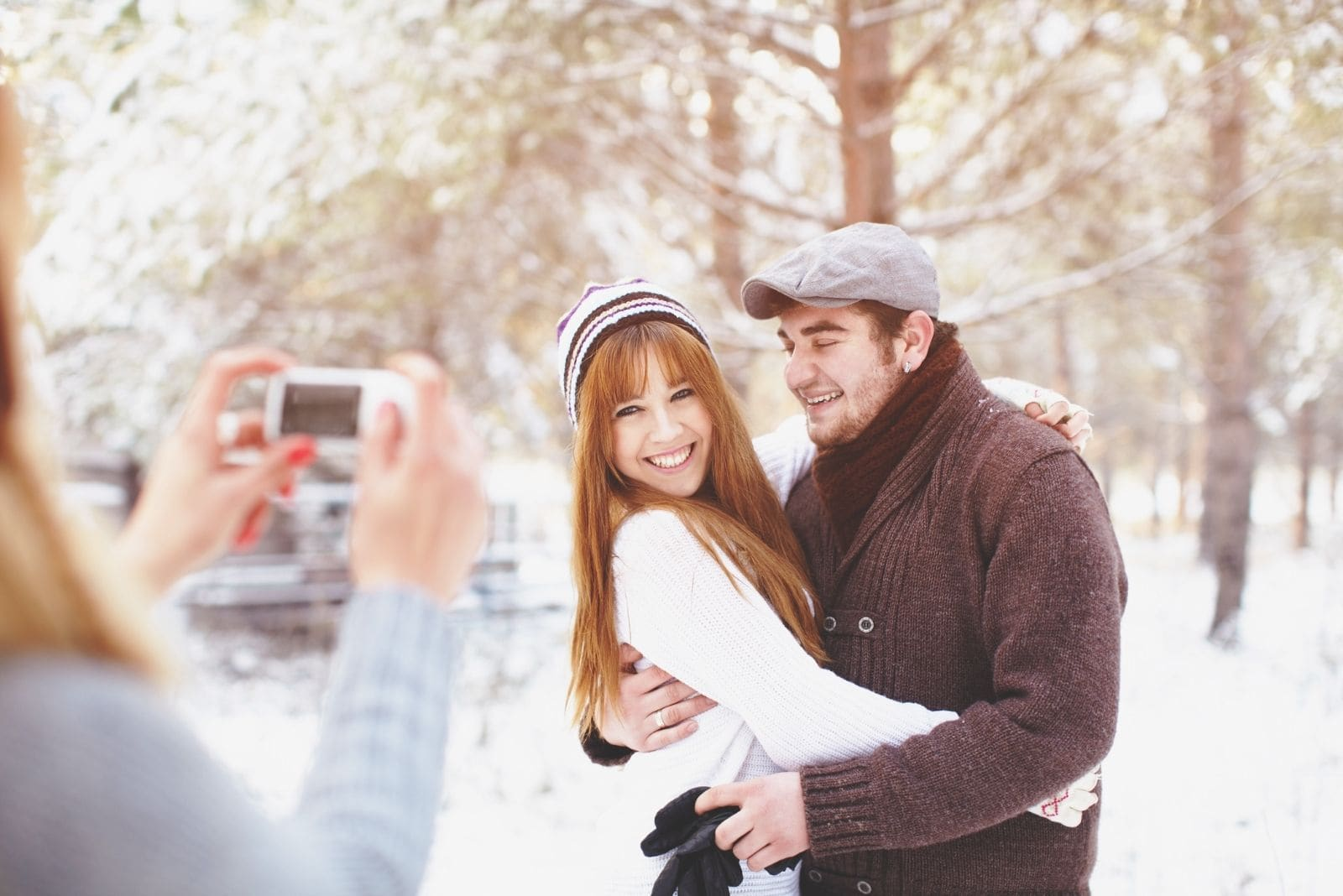 woman taking a picture of a sweet couple in the winter park