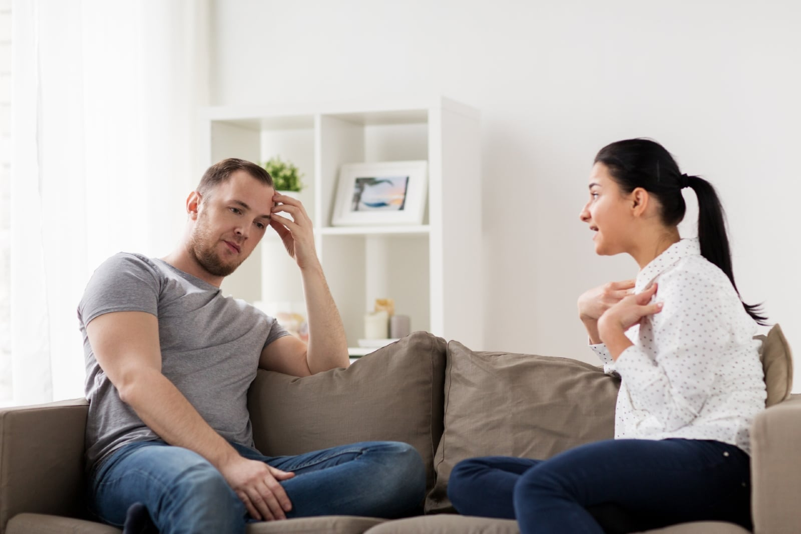 angry woman talking to man while sitting on sofa