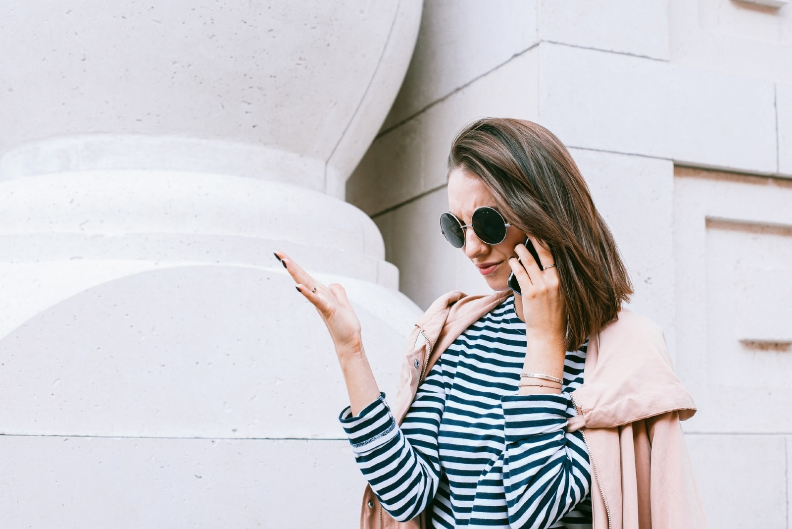 woman in striped shirt talking on the phone outdoor