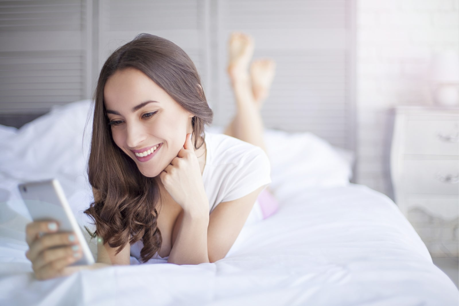 woman using smartphone while laying on bed