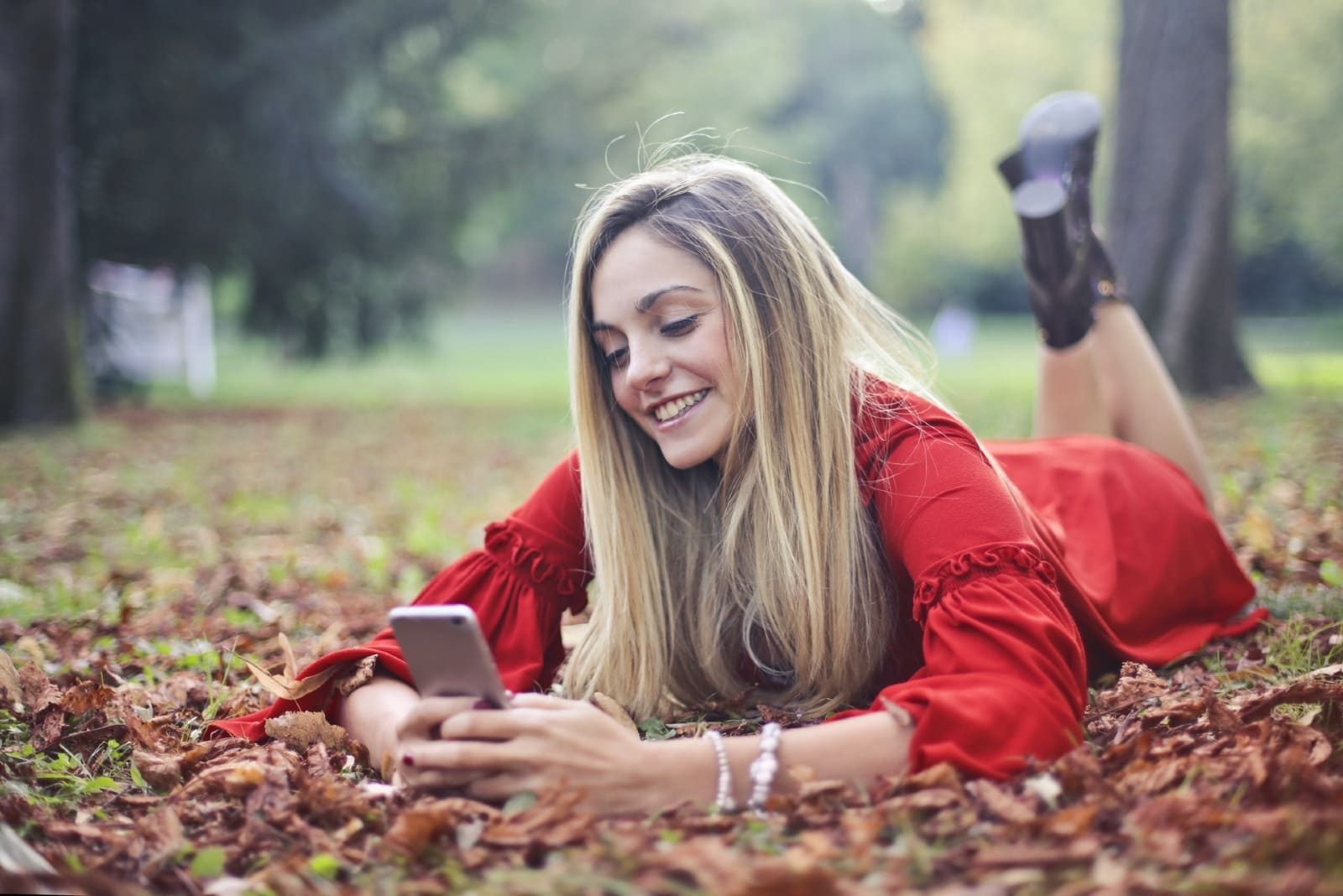 blonde woman using smartphone while laying on leaves