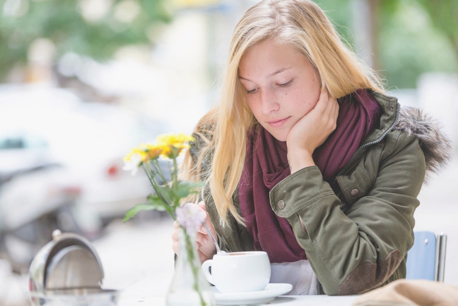 woman waiting in cafe outside lost in thoughts and mixing her coffee