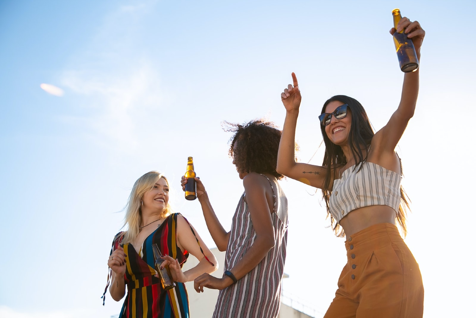 three women drinking beer while dancing on rooftop