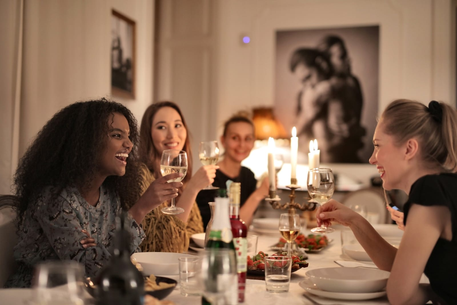 women holding glasses of wine while sitting at table