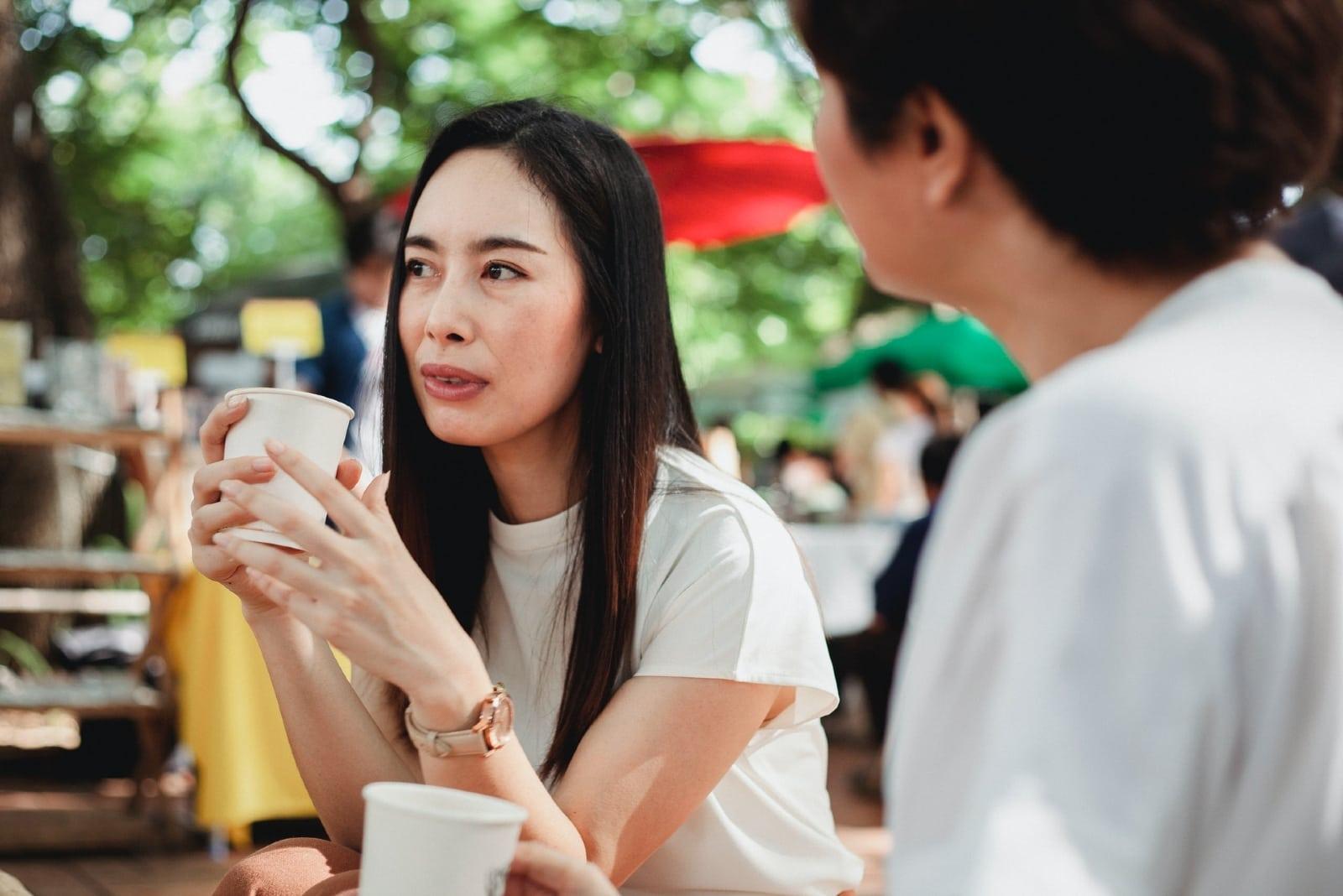 two women talking while having coffee