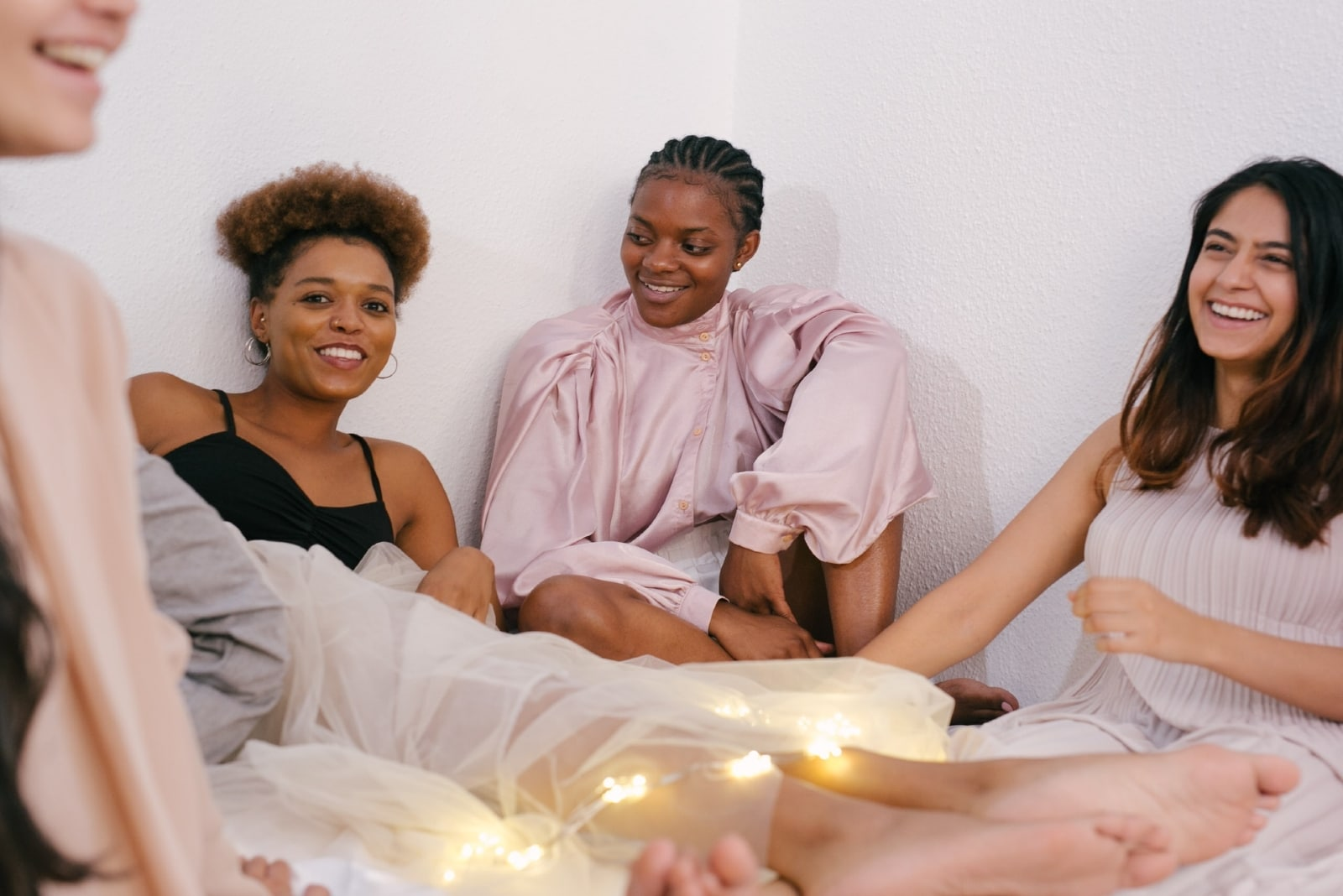 four women talking while sitting on bed