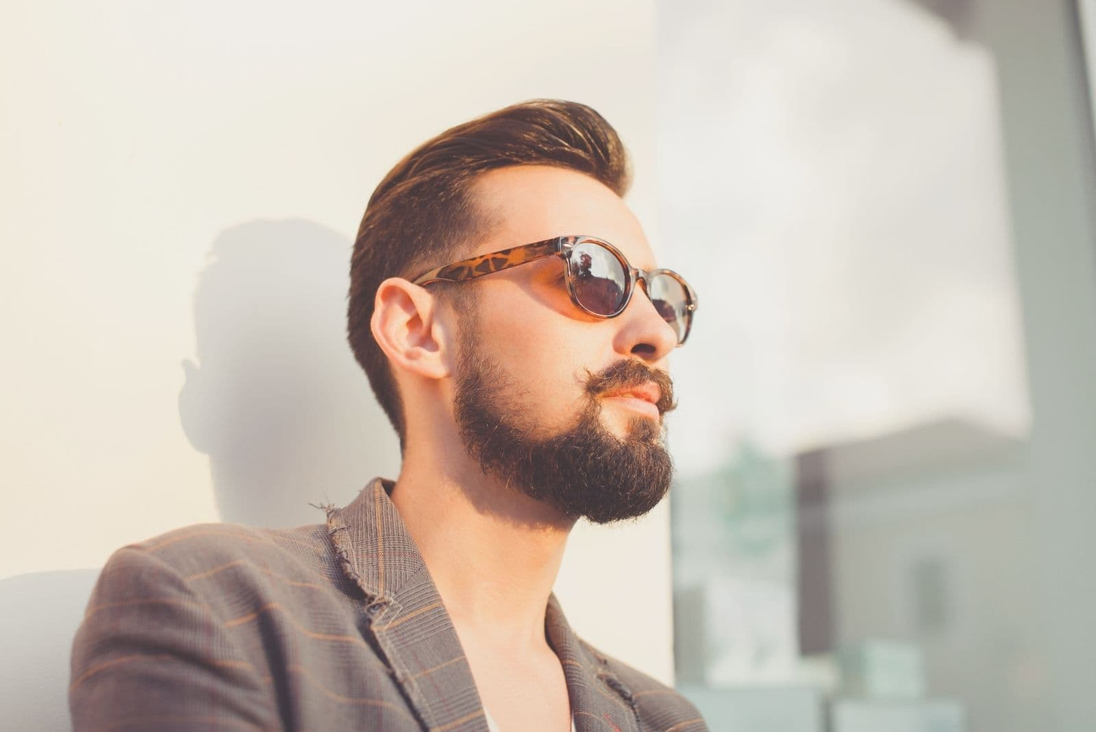 young bearded man standing outdoors in fashion
