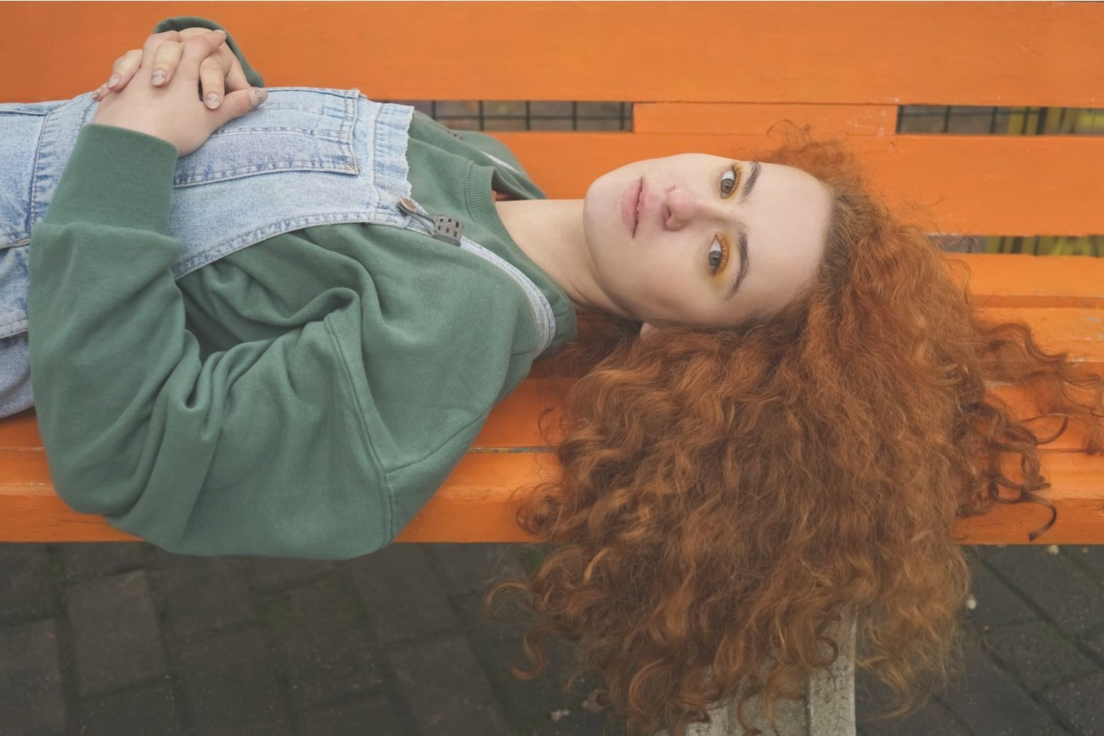 young beautiful redhead woman lying down in the park's bench
