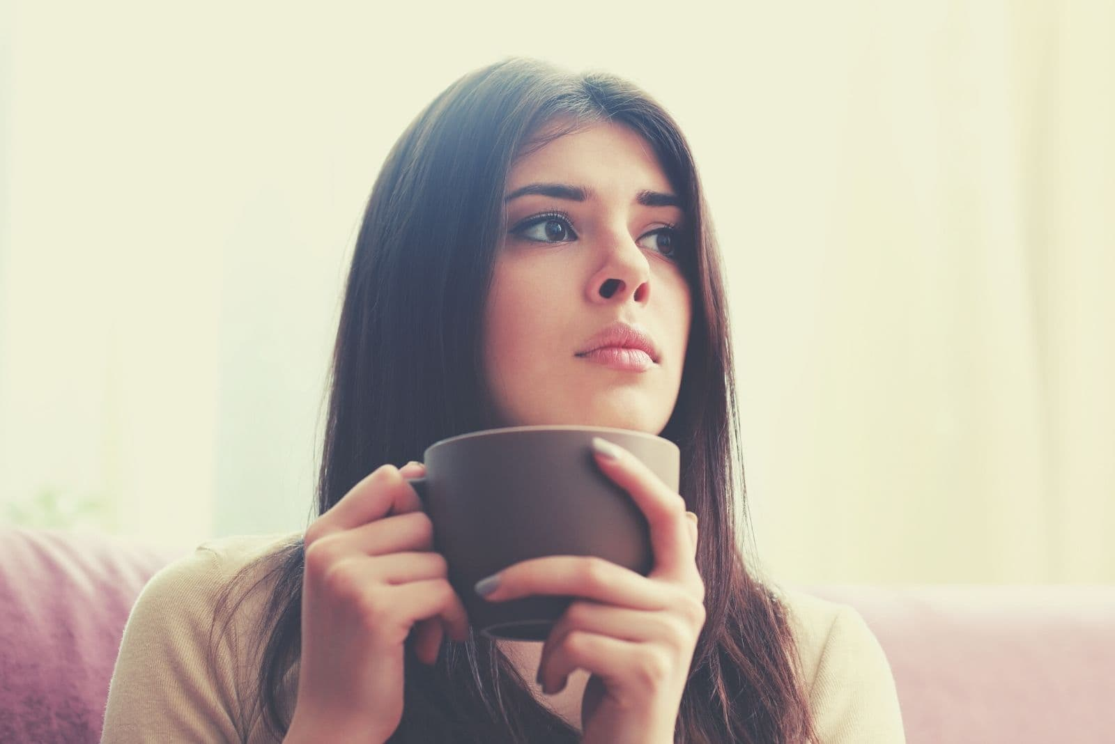 young brunette woman thinking deeply while drinking coffee inside home