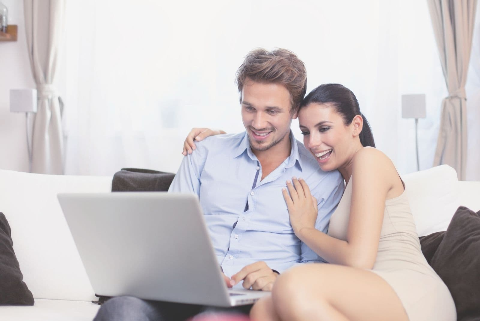 young couple in the livingroom looking at the laptop