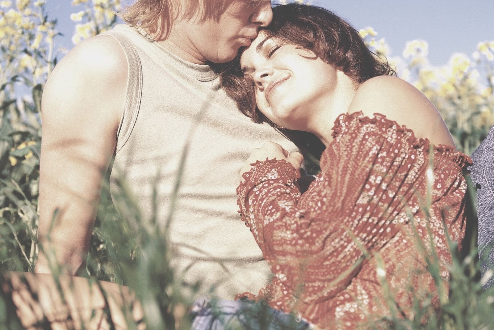 young couple sitting in field of flowers with woman lying in the man's chest while kissing her in the forehead