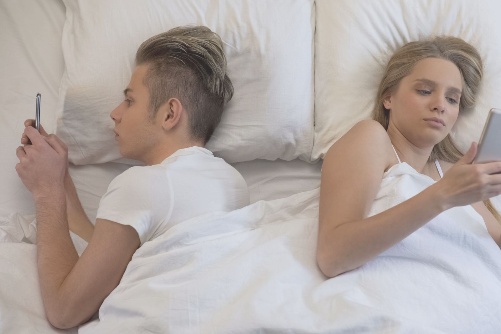 young couple surfing the net while lying down in bed back to back