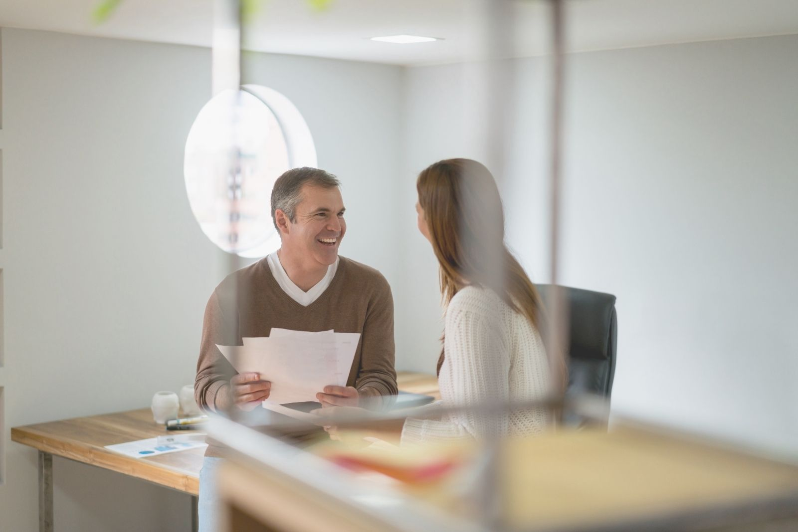 young couple worker talking inside the office laughing